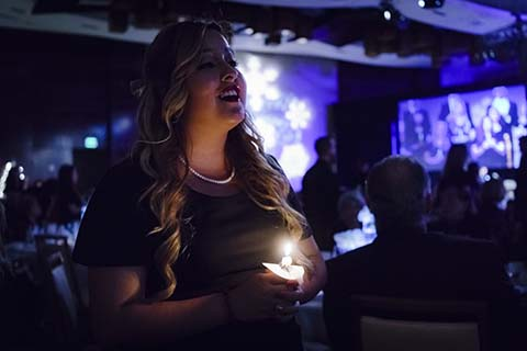 A woman in a black dress holds a candle during an event