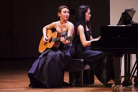 A woman with a guitar sits with a woman who is playing the piano