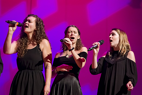Three vocalists in black dresses hold up microphones as they perform on stage